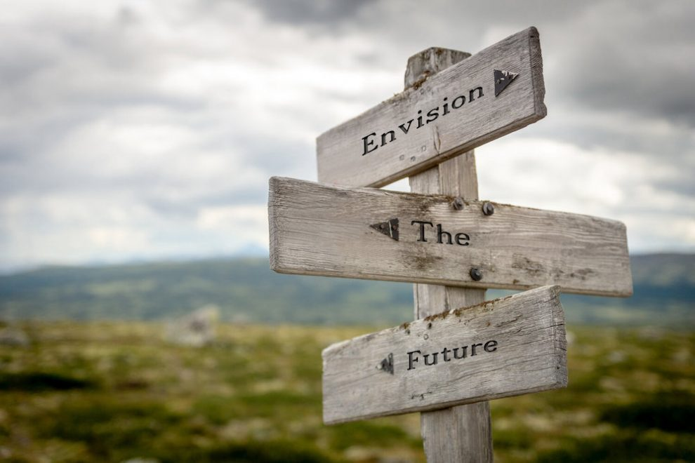 envision the future text on wooden signpost outdoors in nature